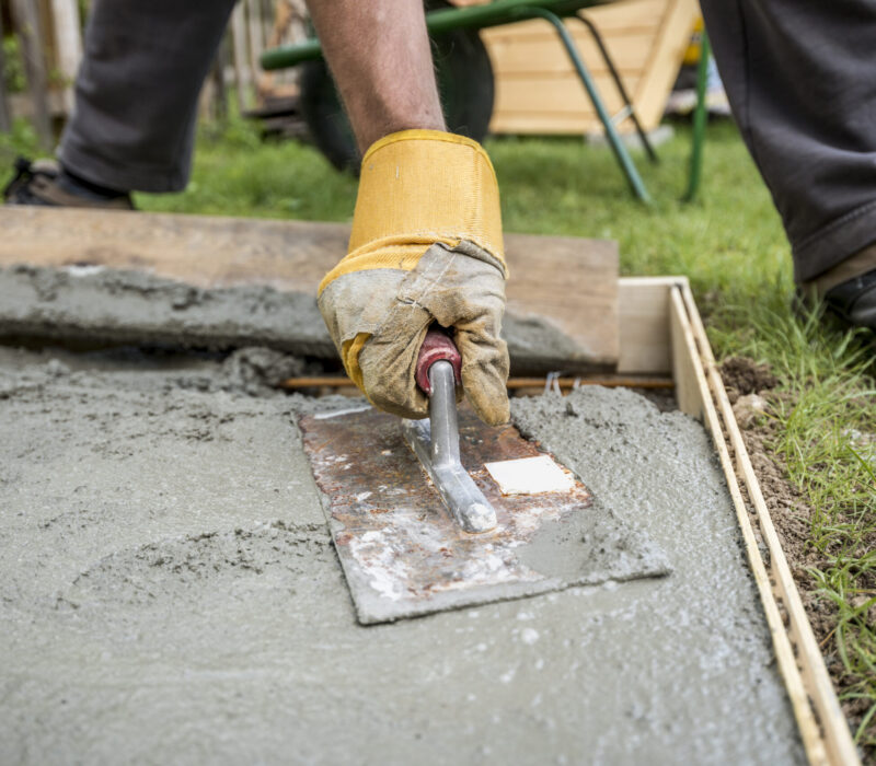 Close up on worker paving or smoothing fresh concrete in plywood walls to be used for an outdoor patio, driveway or sidewalk.