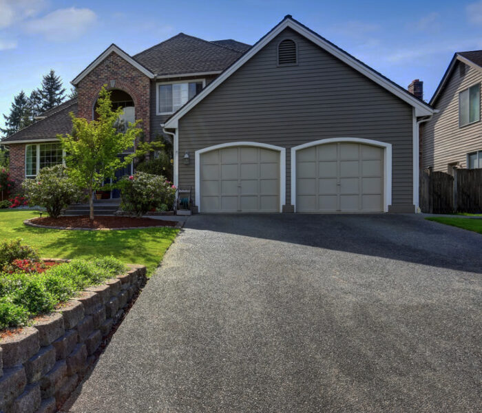 Luxury house exterior with brick and siding trim and double garage. Well kept garden around. Northwest, USA